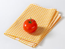 Checked tea towel and red tomato Royalty Free Stock Images