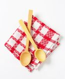 Checked tea towel and wooden spoons Stock Photos