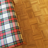 Checked textile banquette on parquet floor Royalty Free Stock Photo