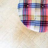 Checked velvet stool on tiled floor Royalty Free Stock Photography