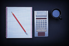 Checked workbook pencil calculator and cup of Stock Image
