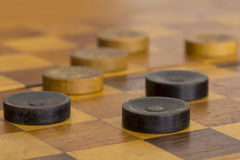 Checker board with checkers. Close up of some old checkers on checker board stock photos