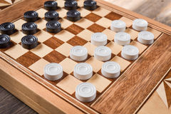 Checker board with checkers on wooden background . Nsport royalty free stock photos