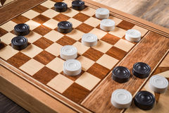 Checker board with checkers on wooden background . Nsport royalty free stock image