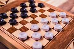 Checker board with checkers on wooden background . Sport stock photography