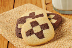 Checker board cookies and milk. Checker board cookies on a napkin with milk royalty free stock photo