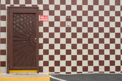 Checker Board with Door. A checker board wall painted white and brown and a metal door royalty free stock images