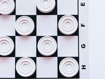 Checkerboard with checkers. Business strategy competition, strategic planning for winning success. Hobby. Checkers on the playing field for a game. Black and royalty free stock photo