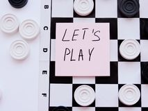 Checkerboard with checkers. Business strategy competition, strategic planning for winning success. Hobby. Checkers on the playing field for a game. Black and stock photos
