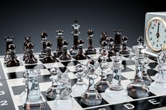 Checkerboard with glass chess figures and chess clock, 3D render. Checkerboard with glass chess figures and chess clock, 3D Stock Images