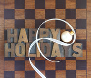 Checkerboard with happy holidays and ornament. Brown and black game board with the words 'Happy Holidays' and an ornament and ribbon Royalty Free Stock Photography