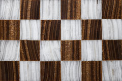Checkerboard in marble made by hand. Close up of a marble chessboard made by hand royalty free stock photo