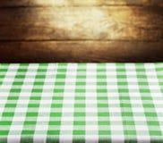 Checkered зеленая скатерть над деревянной предпосылкой Стоковые Изображения