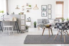 Checkered, стильный стул на сером половике в просторном, scandinavi стоковое изображение rf
