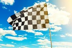 Checkered флаг развевая в ветре с пирофакелом солнца видимым Стоковое Изображение RF