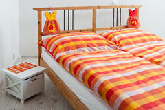 Checkered bedding in interior of bedroom Stock Photography