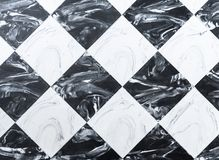 Checkered black and white marble floor tiles background stock image
