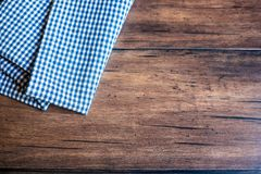 Checkered blue napkin on an old wooden brown background, top view. Image with copy space. Kitchen table with a towel - top view wi. Th copy space royalty free stock photos