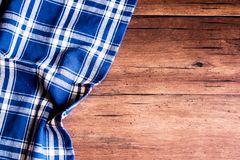 Checkered blue napkin on an old wooden brown background, top view. Image with copy space. Kitchen table with a towel - top view wi. Th copy space stock photos