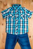 Checkered blue shirt and jeans for boy set on a wooden floor top. View Stock Image