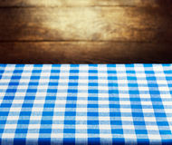Checkered blue tablecloth over wooden background Royalty Free Stock Photography