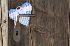 Checkered blue/white heart shape hanging on door handle or a woo. Checkered heart shape hanging on door handle or a wooden Background, country style, shabby chic Stock Photo