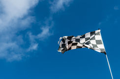 Checkered or chequered flag used in Motorsport. Motorsport background with checkered flag and blue sky royalty free stock images