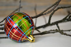 Checkered Christmas ball and twigs Royalty Free Stock Photo