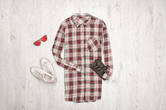Checkered female shirt, black handbag, white sneakers, glasses. Fashionable concept, wooden background.  Royalty Free Stock Image