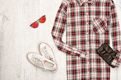 Checkered female shirt, black handbag, white sneakers, glasses. Fashionable concept, wooden background Royalty Free Stock Images