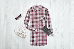 Checkered female shirt, black handbag, white sneakers and sungla Royalty Free Stock Image