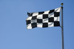 Checkered Finish Line Flag on Pole. A finish line flag on a pole at a raceway Royalty Free Stock Photography