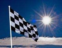 Checkered Flag. High resolution image of a checkered flag. With bright sun and blue sky. Detailed fabric texture and transparency. Copy space included Royalty Free Stock Images