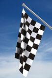 Checkered flag. A view of a checkered flag used to signal the end of a race hanging from a short flag pole against a blue sky with thin white clouds. Clipping royalty free stock photography