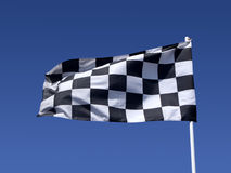 A checkered flag. A checkered flag blowing in the wind at the end of a motor race Stock Photos