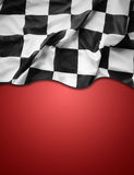 Checkered flag. Checkered black and white flag on red background. Copy space stock image