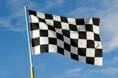 Checkered flag with blue sky. On background Stock Image