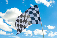 Checkered flag on flagpole with white clouds on background Stock Image