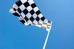 Checkered flag flying on blue sky background Royalty Free Stock Photography