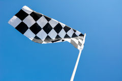 Checkered flag flying on blue sky background Royalty Free Stock Image