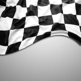 Checkered flag on grey. Checkered black and white flag on grey background. Copy space Stock Photos