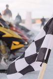 Checkered flag snowmobile race. Closeup of a black and white checkered flag at a racing event with snowmobiles in the background Royalty Free Stock Image