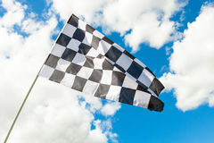 Checkered flag waving in the wind - clouds on background Stock Photography