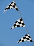 Checkered flags. Several Checkered flags against a clear blue sky Stock Image