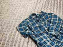 Checkered flannel shirt. Men's casual checkered shirt on the bed Royalty Free Stock Images