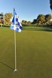 Checkered golf flag on a green Stock Photo
