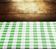 Checkered green tablecloth over wooden background Stock Images