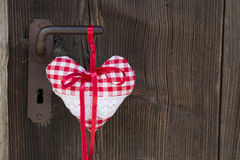 Checkered heart shape hanging on rusty door handle for valentine Royalty Free Stock Image