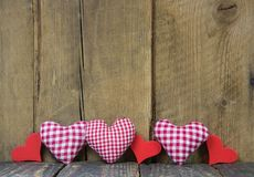 Checkered hearts on wooden background. Royalty Free Stock Images