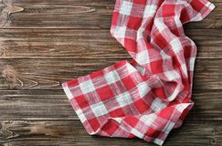 Checkered kitchen towel. On wooden table Stock Images
